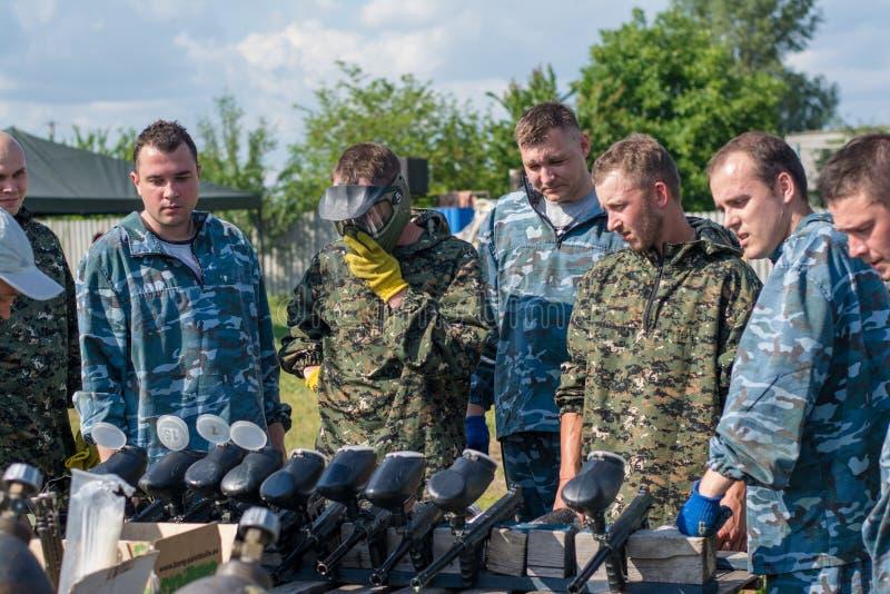 Игроки пейнтбола в камуфлировании выбирая оружия стоковые фотографии rf