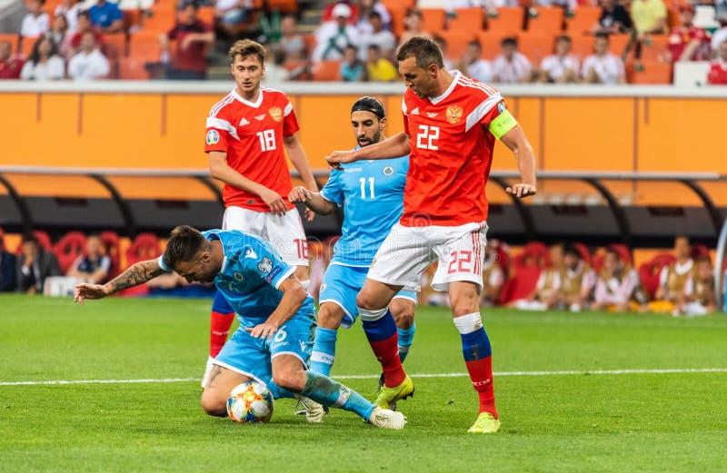 Игроки Anton Miranchuk и Artem Dzyuba России против игроков Fabio Vitaioli и Манюэль Battistini Сан-Марино стоковые изображения
