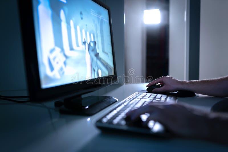 Игрок видеоигры играя видеоигру fps онлайн Гай с компьютером настольного ПК Концепция Esports, течь или cybersport стоковое изображение