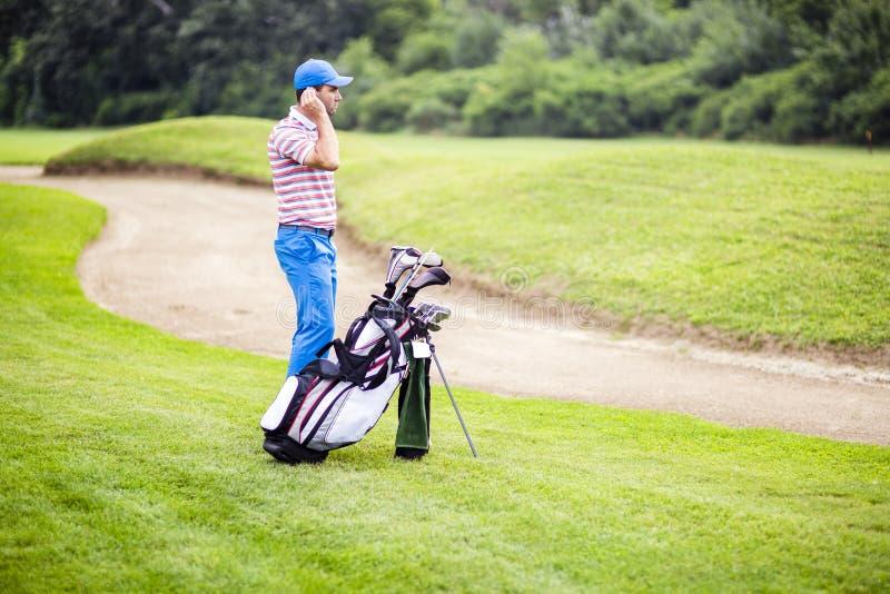 Игрок в гольф выбирая соотвествующий клуб стоковое фото