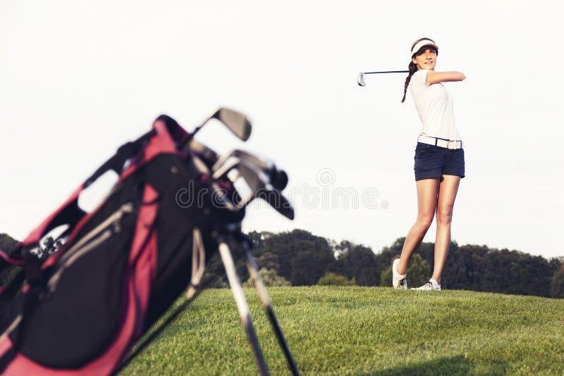 Игрок в гольф девушки ударяя шарик на поле для гольфа. стоковые фотографии rf