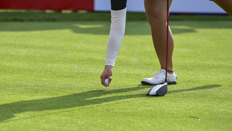Игрок в гольф нажимает шар для игры в гольф гольф-клубом от коробок тройника на поле для гольфа в игре конкуренции стоковая фотография