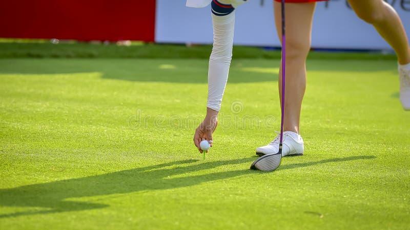 Игрок в гольф нажимает шар для игры в гольф гольф-клубом от коробок тройника на поле для гольфа в игре конкуренции стоковое изображение rf