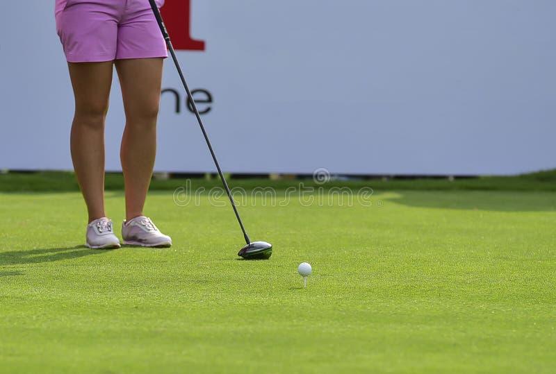 Игрок в гольф нажимает шар для игры в гольф гольф-клубом от коробок тройника на поле для гольфа в игре конкуренции стоковое фото