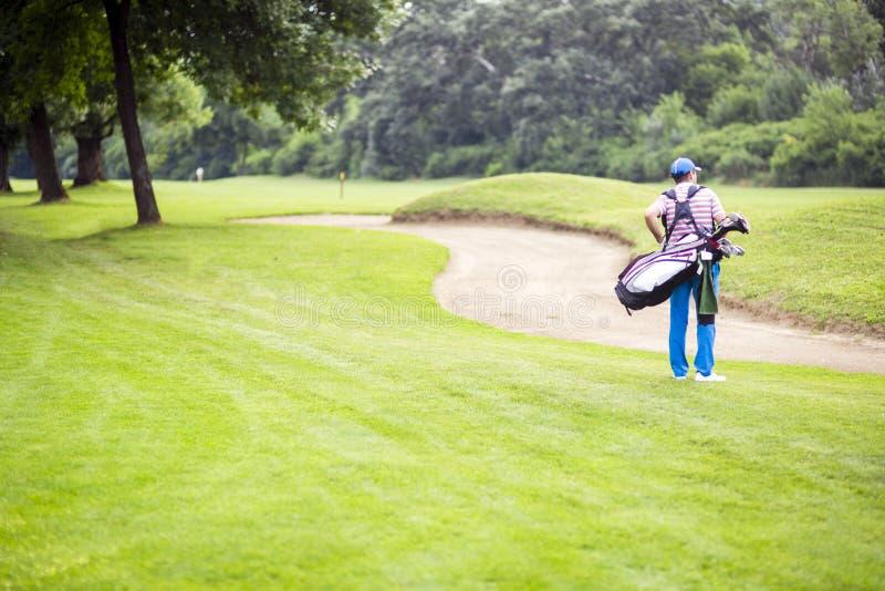 Игрок в гольф нося его оборудование стоковая фотография