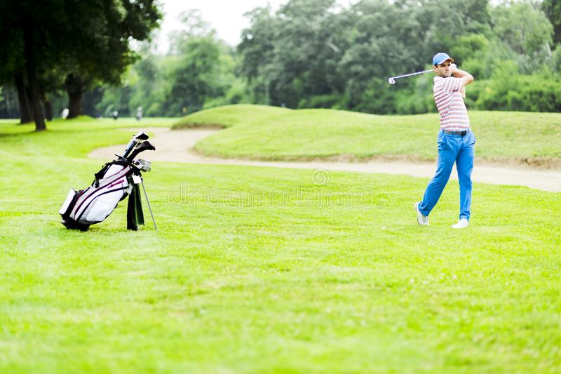 Игрок в гольф практикуя и концентрируя перед и после съемкой стоковые изображения rf