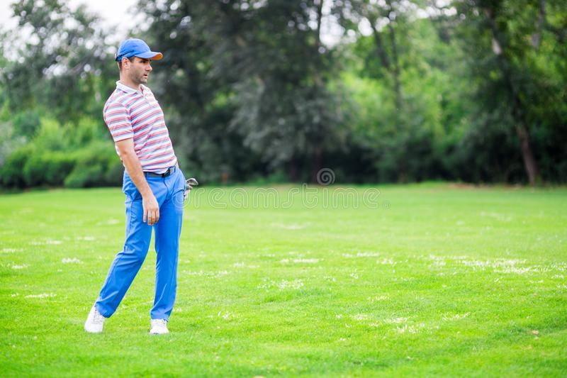 Игрок в гольф практикуя и концентрируя перед и после съемкой стоковая фотография rf