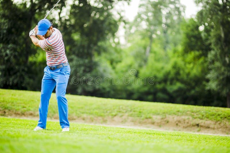 Игрок в гольф практикуя и концентрируя перед и после съемкой стоковое фото rf