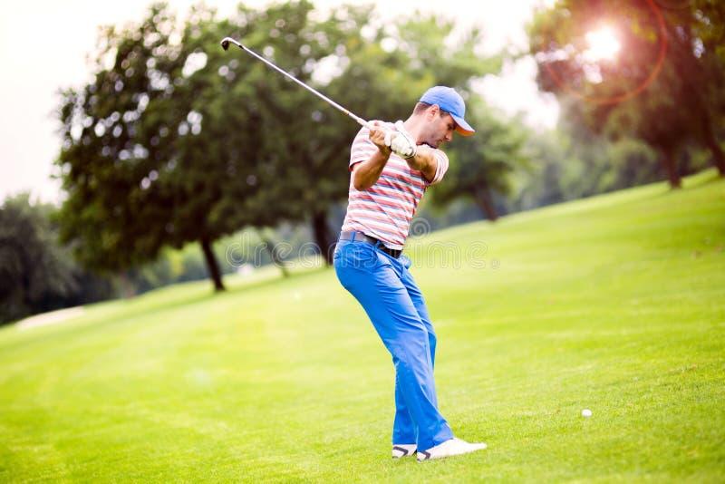 Игрок в гольф практикуя и концентрируя перед и после съемкой стоковые фотографии rf
