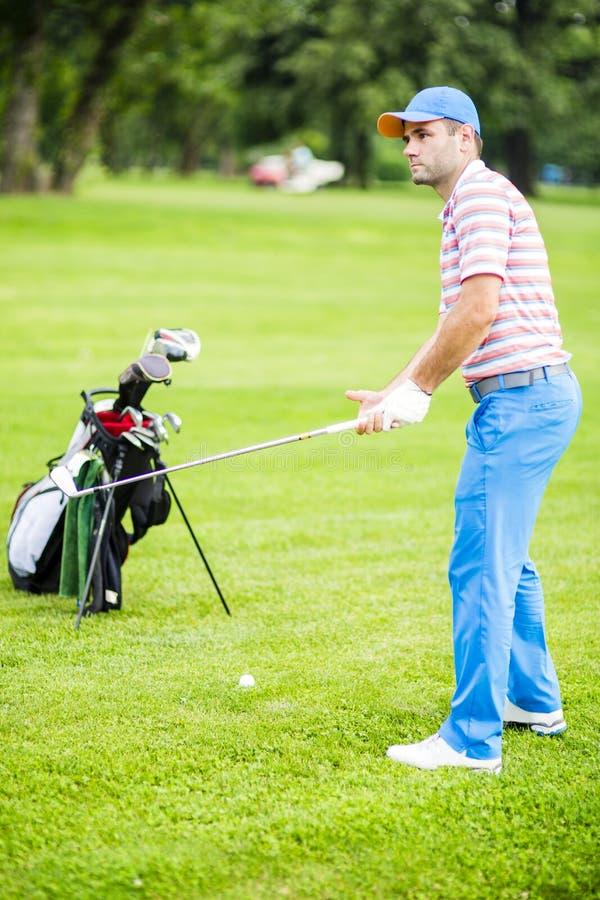 Игрок в гольф практикуя и концентрируя перед и после съемкой стоковые фото