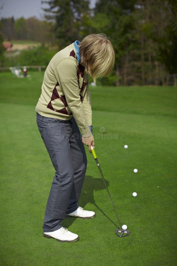 игрок в гольф практикуя кладущ женщину стоковое изображение rf