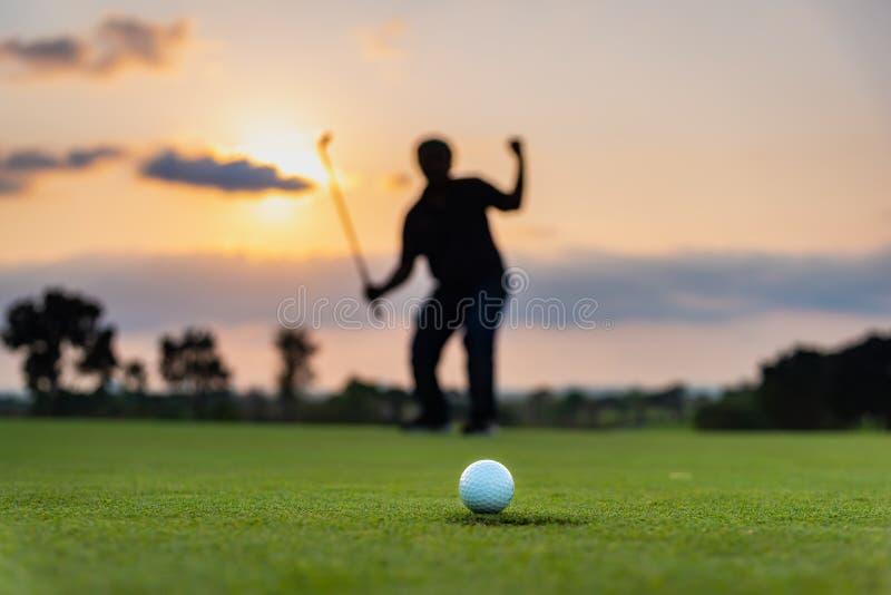 Игрок в гольф силуэта показывая счастье когда выигрыш в игре, белом шаре для игры в гольф на зеленой траве поля для гольфа стоковая фотография