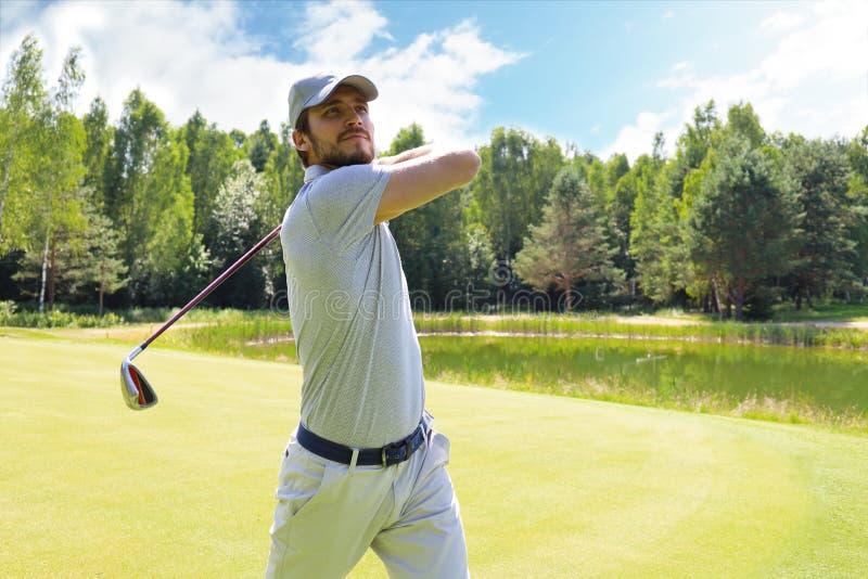 Игрок в гольф ударяя съемку гольфа с клубом на курсе пока на летних каникулах стоковые фотографии rf