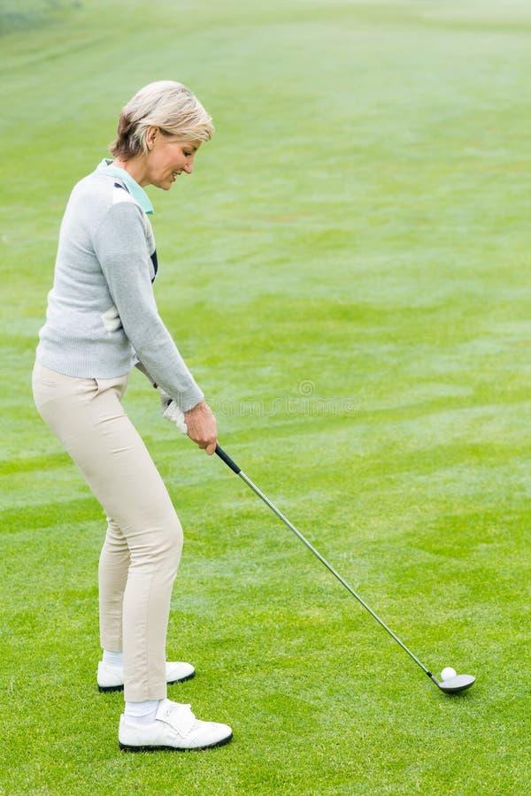 Игрок в гольф дамы на зеленом цвете установки стоковое фото rf