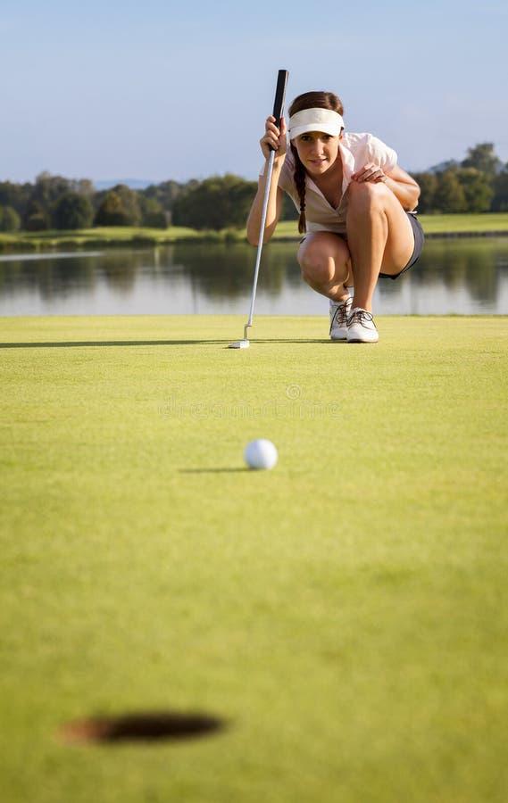 Игрок в гольф анализируя зеленый цвет для установки шарика в чашку стоковое изображение rf
