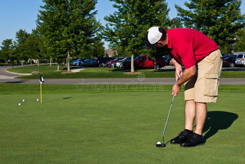 Игрок в гольф практикуя кладущ шары для игры в гольф стоковое фото