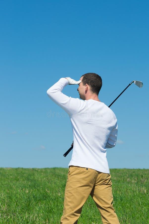 Игрок в гольф смотря прочь защитительно от руки солнца стоковая фотография rf