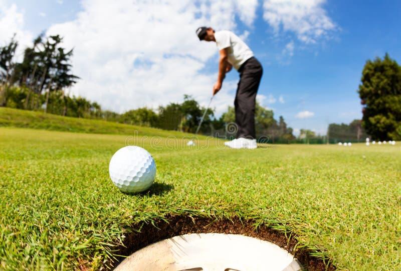 Игрок в гольф управлял шариком в отверстие на зеленом цвете установки; солнце лета стоковые фото