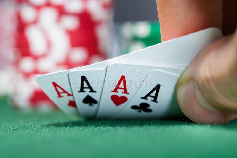 Игрок в покер держа играя карточки стоковое изображение