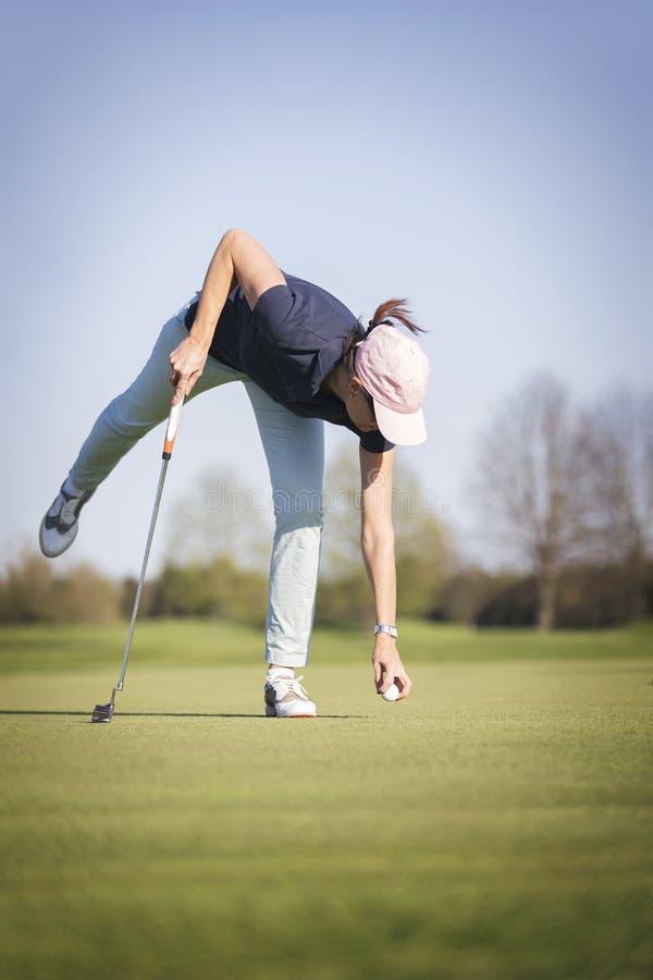 Игрок гольфа женщины выбирает вверх шарик стоковые фотографии rf