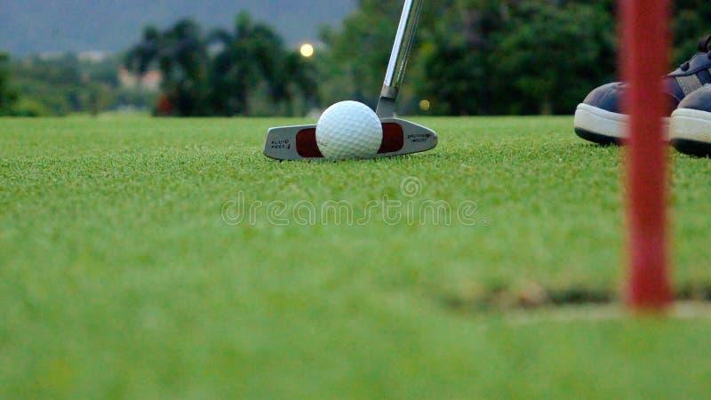 Игрок гольфа кладя шарик в отверстие, только ноги и утюг, который нужно увидеть стоковое изображение rf