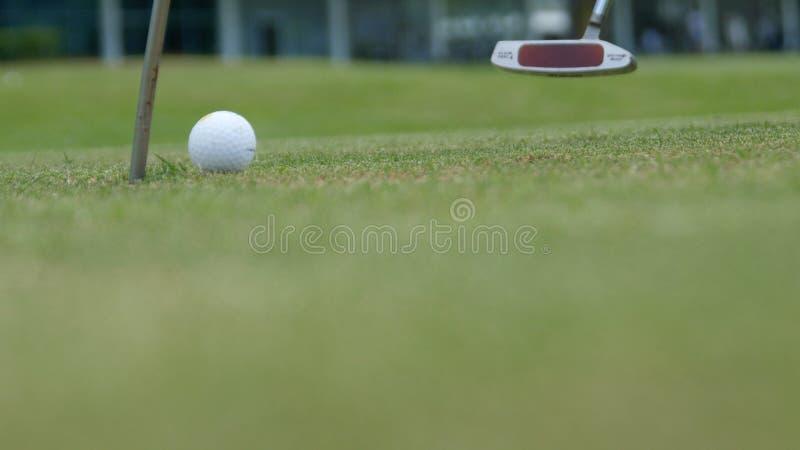 Игрок гольфа кладя шарик в отверстие, только ноги и утюг, который нужно увидеть стоковые изображения
