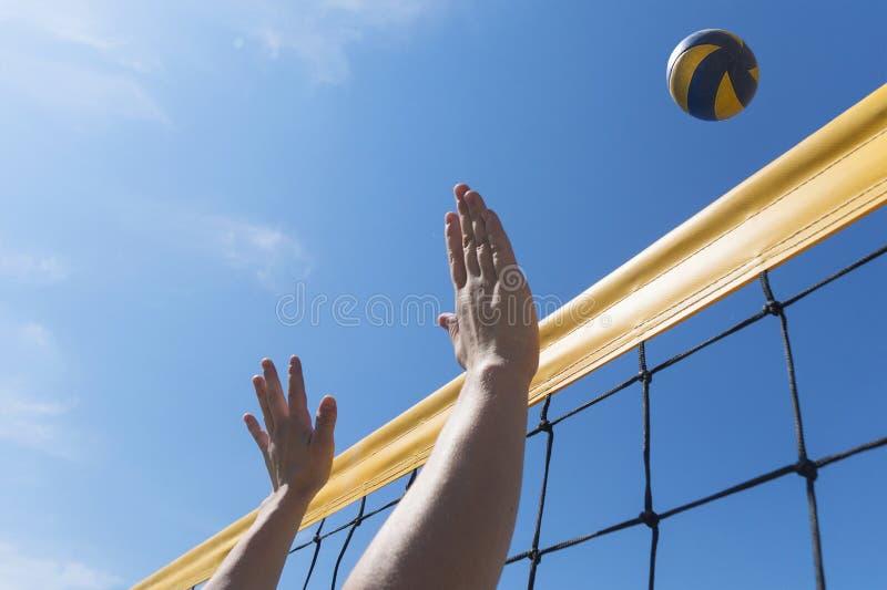 Игрок женщины волейбола пляжа в действии на солнечном дне под голубым небом достигаемость конца-вверх рук для шарика стоковое изображение rf