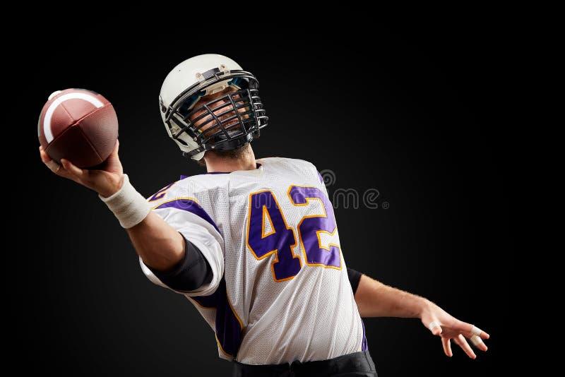 Игрок спортсмена американского футбола на черной предпосылке Концепция спорта стоковое фото rf