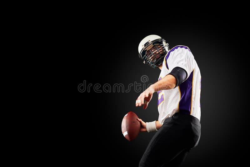 Игрок спортсмена американского футбола на черной предпосылке изолированная принципиальной схемой белизна спорта стоковые фото