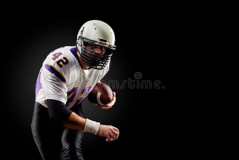 Игрок спортсмена американского футбола на черной предпосылке Концепция спорта стоковая фотография