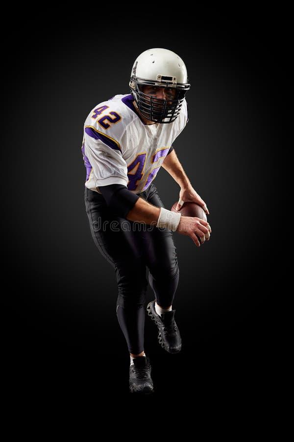Игрок спортсмена американского футбола на черной предпосылке изолированная принципиальной схемой белизна спорта стоковые изображения