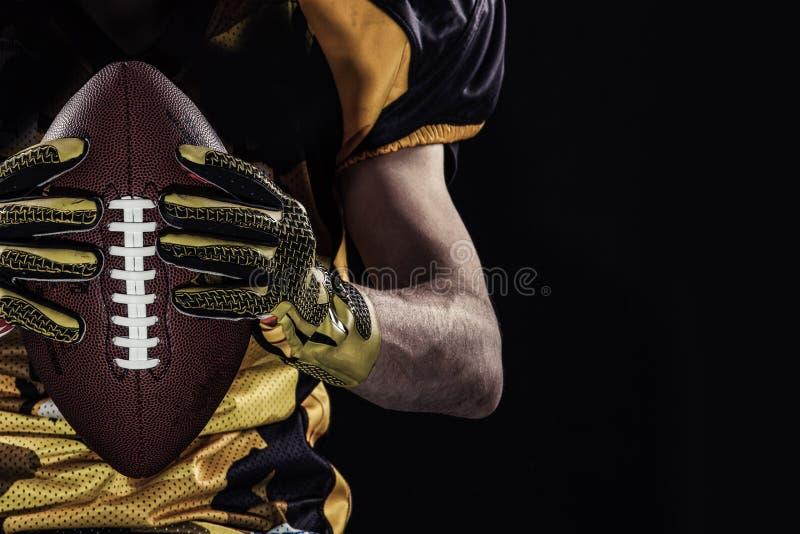 Игрок спортсмена американского футбола на черной предпосылке стоковая фотография rf