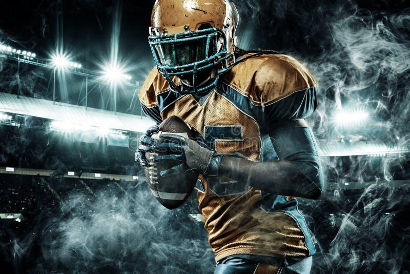 Игрок спортсмена американского футбола на стадионе бежать в действии стоковые фото