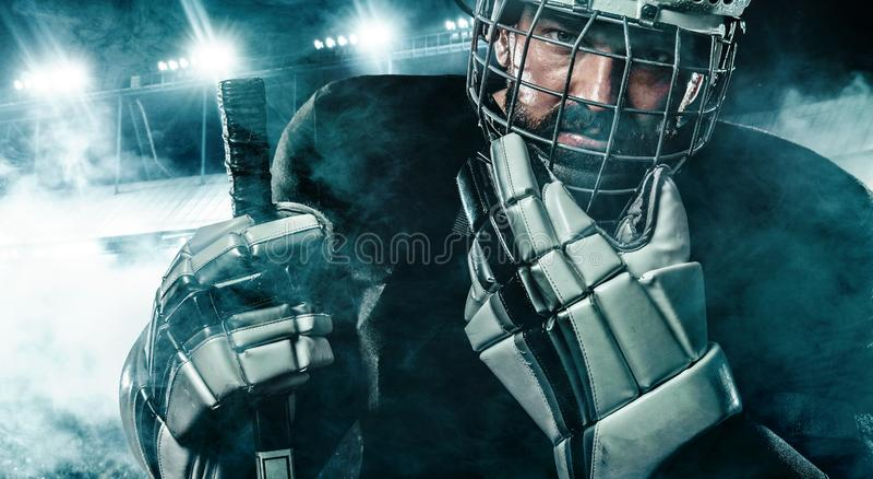 Игрок хоккея на льде в шлеме и перчатки на стадионе с ручкой стоковая фотография
