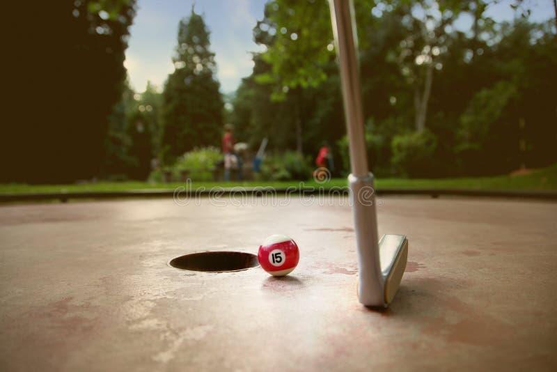 Игрок Minigolf пробует положить малый шарик billard стоковые изображения