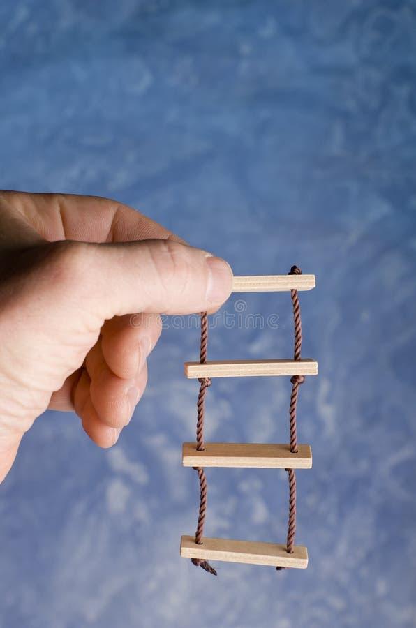 Игрушка лестницы веревочки держа в взрослой руке на голубой предпосылке Взбираться для воображений успеха стоковая фотография rf