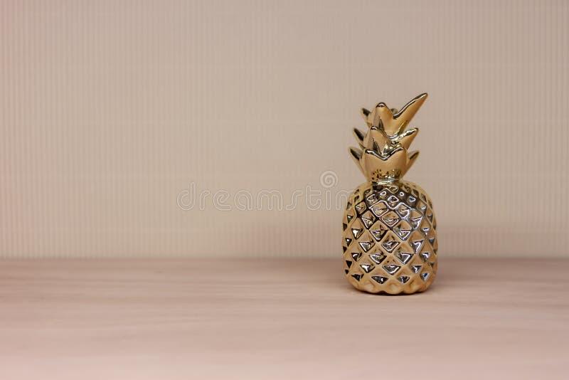 Игрушка золотого ананаса форменная на светлой предпосылке стоковое фото