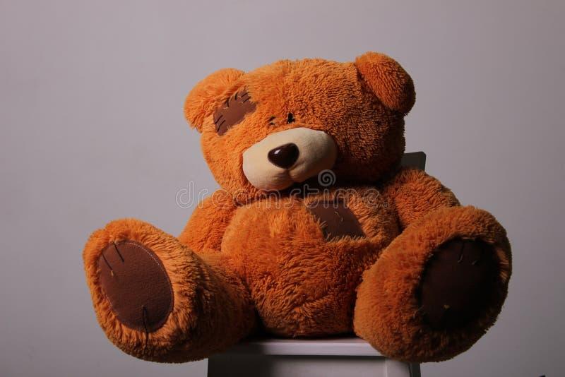 Игрушка медведя коричневая пушистая оранжевая стоковое фото rf