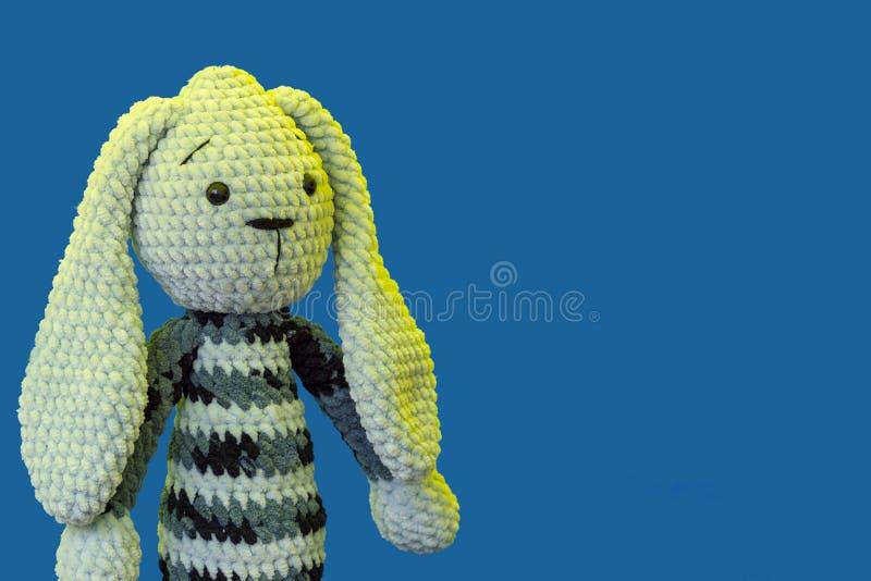 Игрушка связанная зайчиком на голубой предпосылке стоковые изображения
