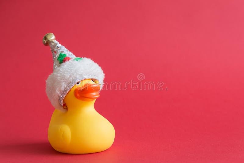 Игрушка утки рождества резиновая для плавать на красной предпосылке стоковое изображение