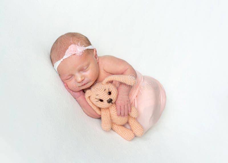 Игрушка Newborn девушки спать и прижимаясь стоковое изображение rf
