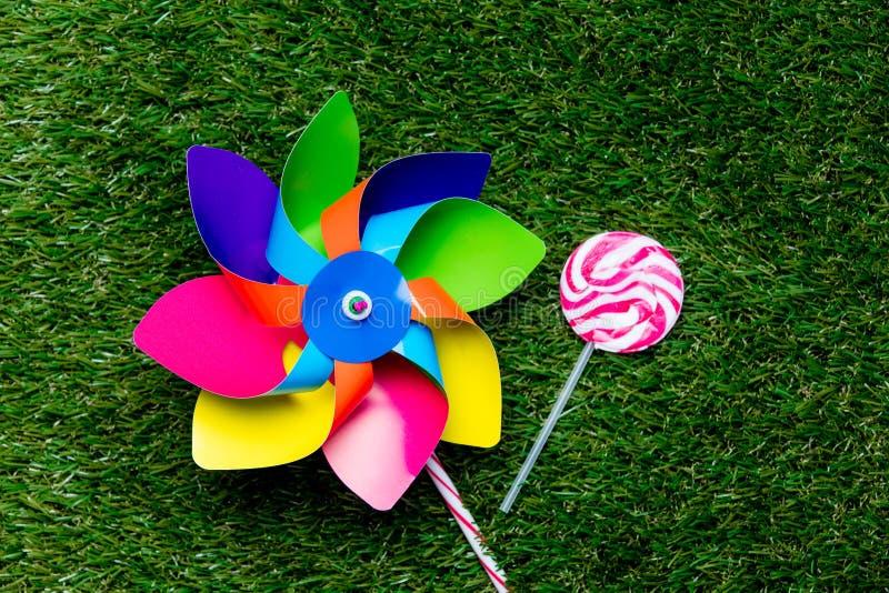 Игрушка Pinwheel и конфета леденца на палочке на предпосылке зеленой травы, стоковое фото rf