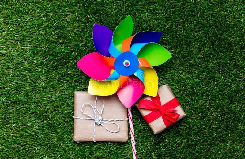 Игрушка Pinwheel и 2 подарочной коробки на предпосылке зеленой травы, выше стоковая фотография rf