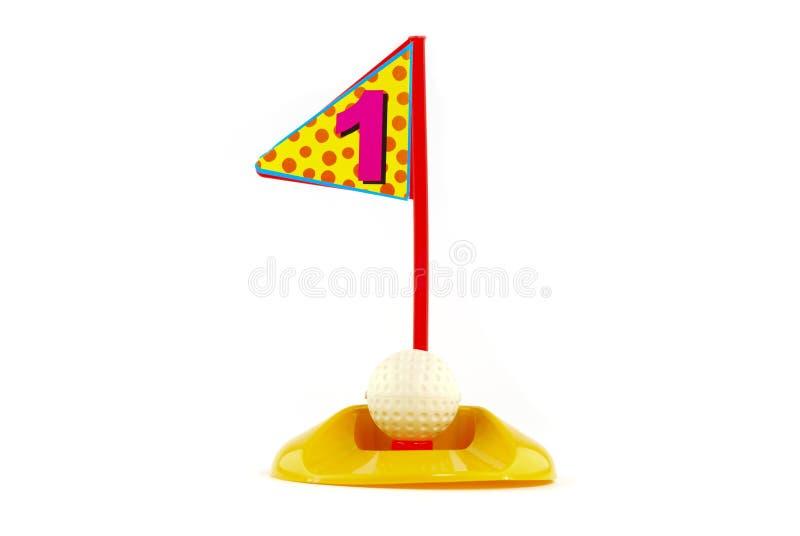 Игрушки гольфа на белизне и владении одно стоковое изображение