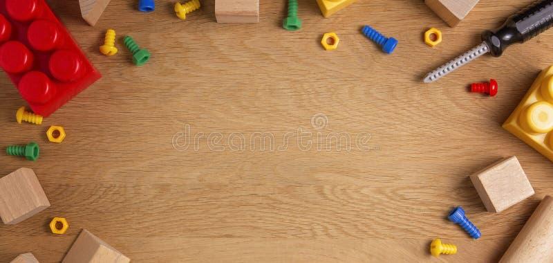 Игрушки детей обрамляют предпосылку с инструментами, блоками и кубами игрушки на деревянном столе r стоковая фотография rf