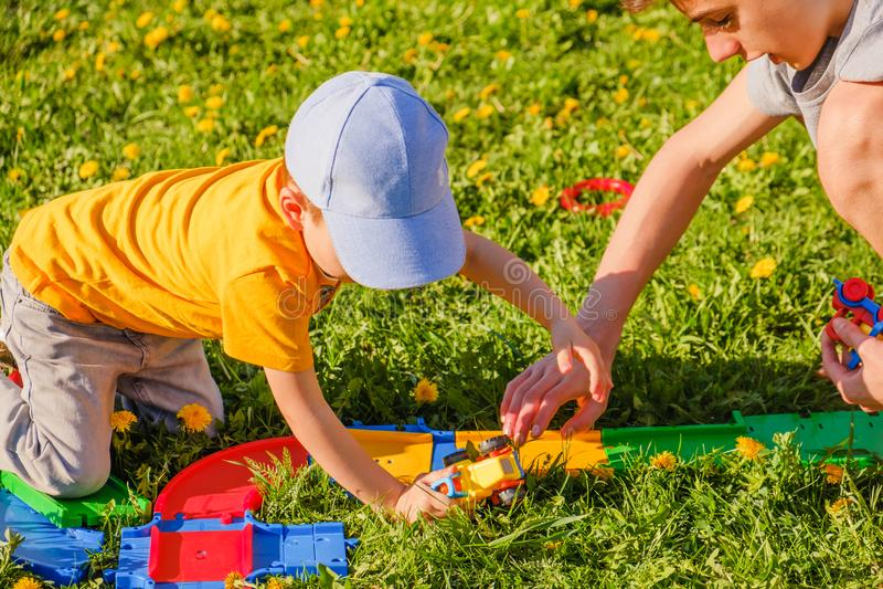 2 игры братьев с автомобилем игрушки на лужайке зеленой травы стоковая фотография rf