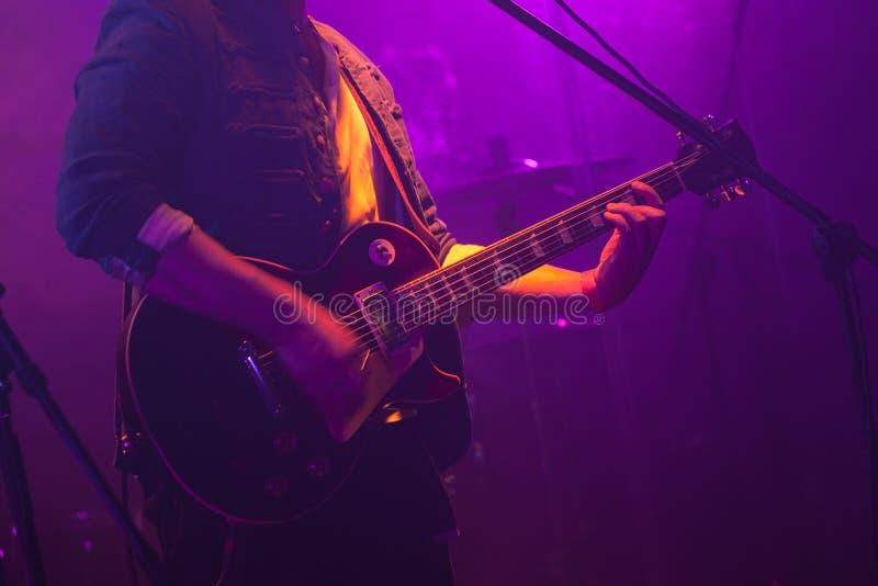 Игры гитариста на гитаре в фиолетовых светах стоковые изображения