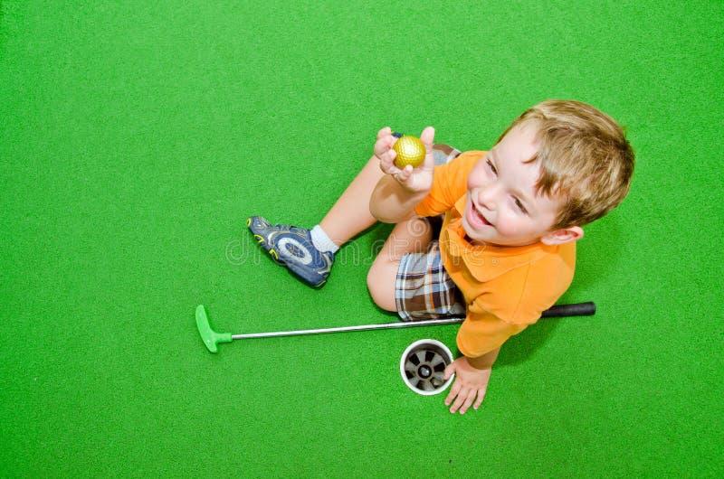 игры гольфа мальчика миниые молодые стоковые изображения