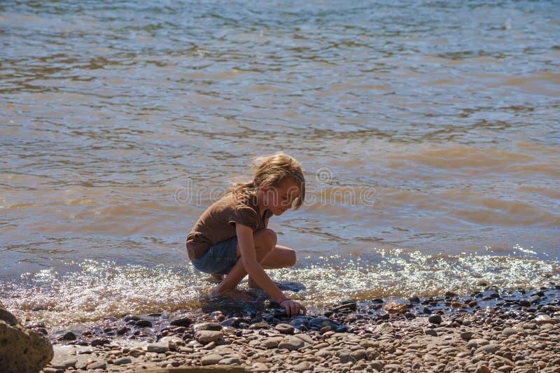 Игры маленькой девочки вдоль берегов реки Willamette стоковое изображение rf