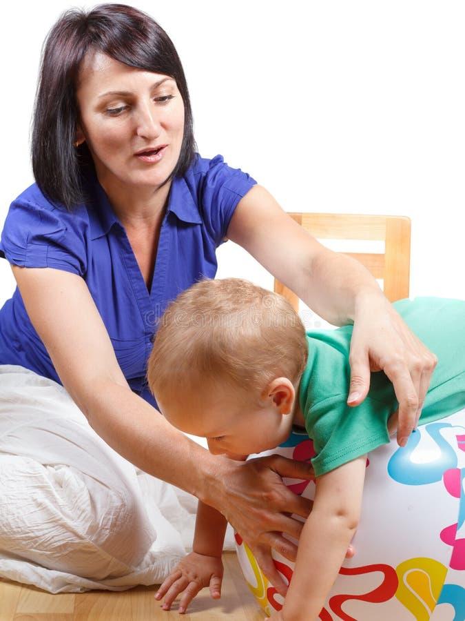 Игры мамы с ее шариком непоседы младенца Изолировано на белизне стоковая фотография rf